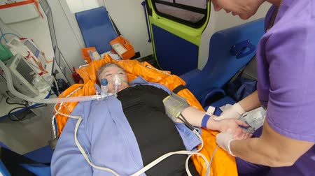 paramedic : EMT female paramedic provide out of hospital medical care to critical senior patient preparing an intravenous infusion in ambulance