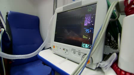 stroke : EMT paramedic provide emergency medical care to person in ambulance monitoring high blood pressure on screen of multiparameter patient monitor pan shot closeup