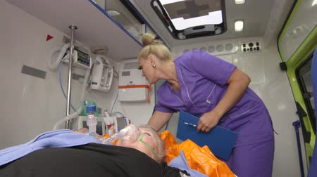 stroke : Paramedic inside the ambulance provide emergency medical care for critical patient transporting senior woman to hospital Stock mozgókép
