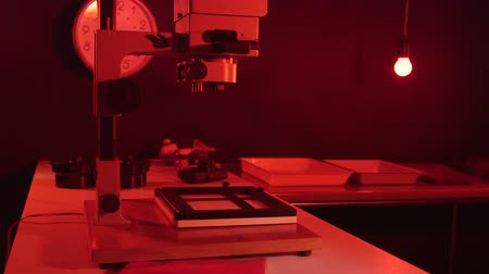 növelni : Photography darkroom with red lighting and equipment for film print processing