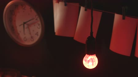 negatives : Red bulb in front of drying pictures in photography darkroom close-up Stock Footage