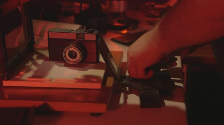 negatives : Man photographer using enlarger in red darkroom to produce photographic prints
