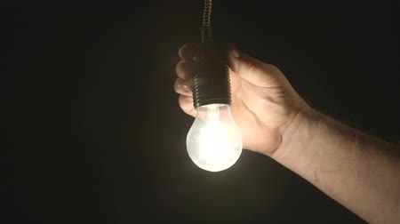 mudança : Hand installing electric light bulb in dark room