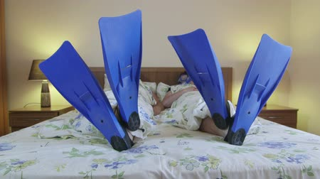 šnorchl : Man and woman scuba divers in flippers and snorkeling mask lying on bed in summer hotel room Dostupné videozáznamy