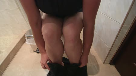 уборная : Woman using roll of toilet paper while sitting on the toilet Стоковые видеозаписи