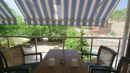 erkély : Shaded balcony of summer hotel with outdoor table and chairs set in cooling shade of retractable awning