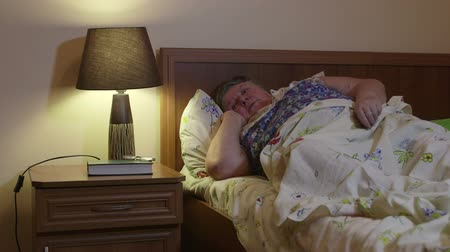 nadváha : Overweight older woman lying in bed talking on phone at night Dostupné videozáznamy
