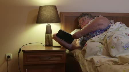 cochilando : Older woman lying in bed reading book before dozing off at night