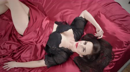 tmavé vlasy : Beautiful brunette woman with long hair in black lingerie lying on dark red silk satin bed looking at camera, top view jib moving up Dostupné videozáznamy