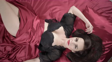 bra : Top view of sexy brunette young woman with perfect makeup in elegant black lingerie on dark red silk satin bed looking at camera, jib moving up Wideo