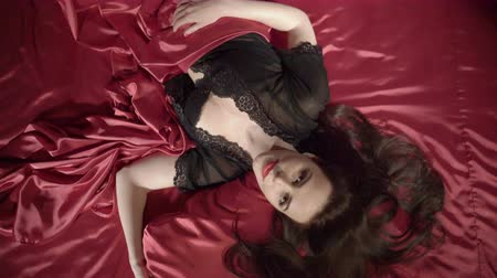 szatén : Top view of sexy brunette young woman with perfect makeup in elegant black lingerie on dark red silk satin bed looking at camera, jib moving up Stock mozgókép