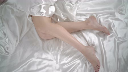 část těla : Top view of young woman sleeping in bed perfect female legs on white silk linen, jib moving up
