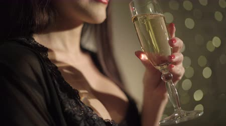 black yellow : Sexy woman in black lingerie holding champagne glass at party drinking wine over holiday glowing background Stock Footage