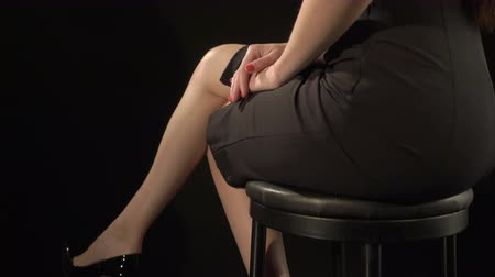 nogi : Elegant young woman in sexy short black bodycon dress and high heel shoes sitting on stool over black background, legs crossed at knee, low section jib moving up