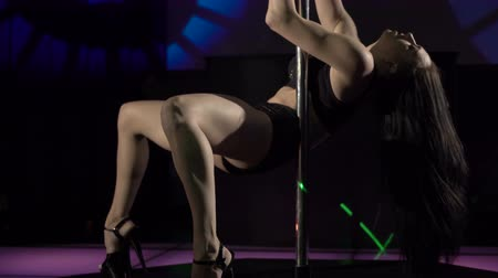 kutuplar : Young strong woman poledancer shows pole dance tricks on lighted stage at dancing night club, zoom inout part 13