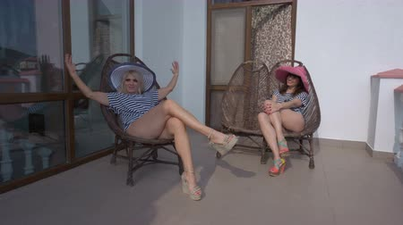 erkély : Two women girlfriends relaxing sunbathing in cane chairs on open terrace at summer hotel resort