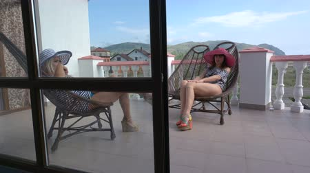 erkély : Two women relaxing in cane chairs on open terrace balcony at vacation home girlfriends spending their holiday together view through the frame glass doors