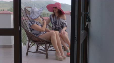 erkély : Two women girlfriends having fun together in cane chairs on open terrace balcony at vacation home, view through the frame glass doors