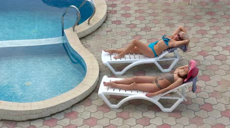 vacation destination : Two smiling women in swimsuits relaxing on sun loungers by private pool at vacation home girlfriends spending their summer vacation together, zoom out long shot high angle view