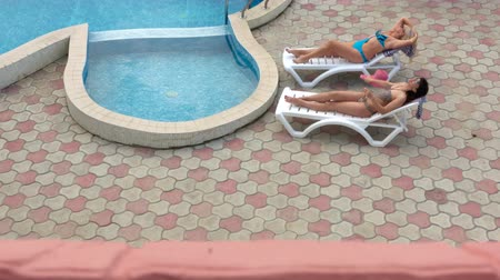 erkély : View from balcony at two women girlfriends in swimsuits relaxing by private swimming pool at summer vacation home, tilt up high angle shot