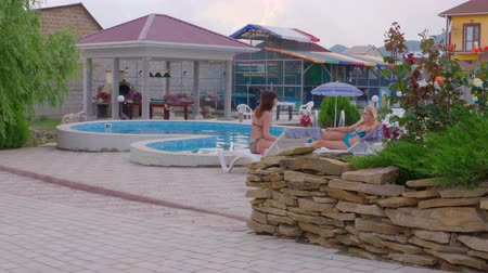 holiday villa : Two women girlfriends relaxing on sun loungers by private swimming pool at summer vacation home pan shot Stock Footage