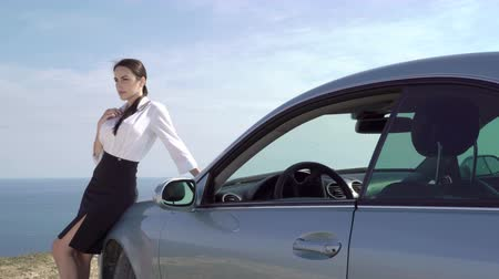 деловая женщина : Relaxed business woman in formalwear leaning on the two-door car parked on the edge of steep cliff at the sea shore looking away in thought, pan shot