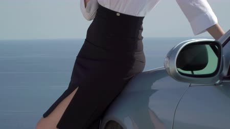 элегантный : Serious business woman dressed in elegant formalwear leaning on her car parked at the edge of cliff by sea looking away in thought, close-up tilt up