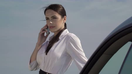 řidič : Attractive business woman dressed in formalwear taking phone call leaning on her car against the sky