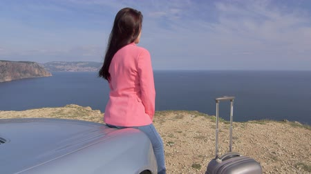 estância turística : Relaxed young woman with travel suitcase leaning on car bonnet on the edge of cliff looking out to sea jib crane shot