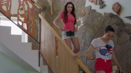 dom : Two young women dressed in jeans shorts and T-shirts walking down flight of stairs in the house one woman smiles and waves her hand looking at the camera