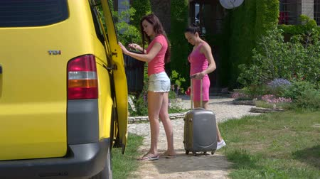 távozás : Two young women tourists arrived by passenger van at summer vacation home or small hotel taking travel suitcases out of car Stock mozgókép