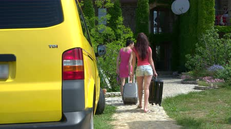 mekik : Young women with luggage on summer vacation arrived at small hotel by passenger van pulling suitcases to the entrance