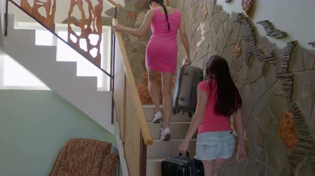 vacation destination : Two young women on summer vacation carrying travel suitcases up stairs in the house