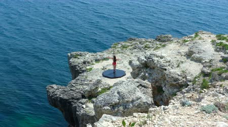 platform edge : Young fit woman in black red bodysuit doing pole dancing fitness exercise performing pole tricks and spins on the edge of rocky cliff by sea high angle extreme long shot episode_1