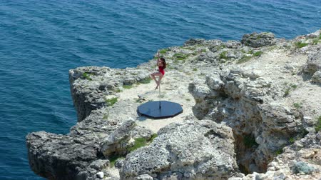 platform edge : Graceful young woman poledancer in black red bodysuit doing pole dancing fitness exercise on edge of rocky cliff performing pole tricks and spins on the edge of rocky cliff by sea extreme long shot episode_3 Stock Footage