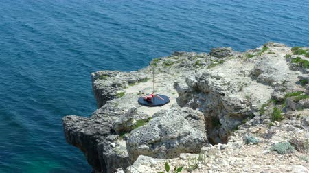 platform edge : Fit young woman poledancer wearing a black red monokini doing pole dancing fitness exercise on the edge of rocky cliff above the sea majestic scenery with clear blue water, extreme long shot episode_5