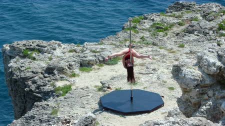 platform edge : Slow motion of young woman poledancer performing trick on the edge of rocky cliff by sea pole dancing as outdoor fitness long shot episode_10