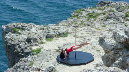 platform edge : Slow motion of young woman poledancer doing pole dancing fitness exercise on the edge of rocky cliff by sea high angle long shot Stock Footage