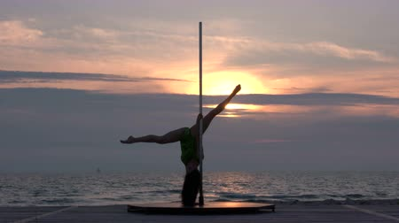 fit : Fit girl poledancer performs fitness pole dance on the portable dancing stage at sunset silhouette of flexible young woman against the setting sun in summer evening