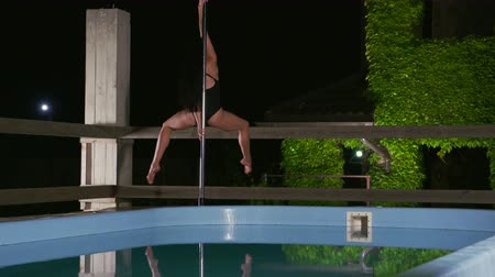 kutuplar : Graceful woman poledance artist performing fitness pole dance outdoors spinning around pole on portable dancing stage beside private pool at night
