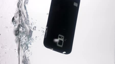 damlatma : Smart phone with blank screen fall down on the vertical water surface dipping underwater slow motion closeup