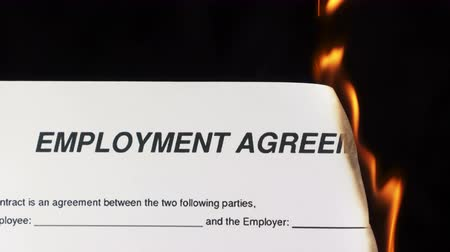 cancellation : Closeup of white sheet of paper with text employment agreement burning in fire on a black background
