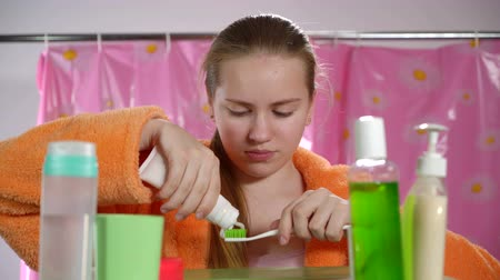 pędzel : Teenage girl in bathrobe brushing her teeth in bathroom looking in the mirror