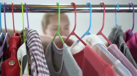 traje de passeio : Closeup of teenage girl thinking what to dress in closet room focus on clothing rack Stock Footage