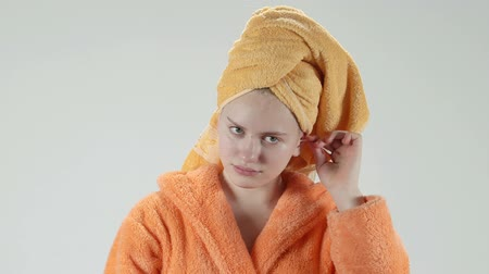 kulaklar : Teenage girl after shower in bathrobe wrapped in a towel on head cleaning her ear with cotton swab looking in mirror