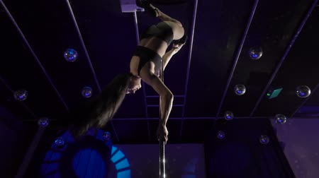 kutup : Pole-dance performance strong girl spinning on top of pole in slow motion