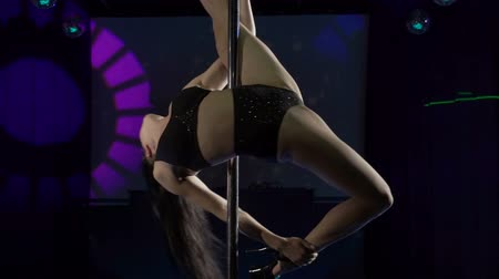 kutup : Graceful girl pole dancer performs acrobatic tricks on lighted stage at night club fit pole-dancer in sports bra and shorts spinning on top of pole in slow motion