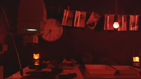 negatives : Photography darkroom with black and white drying pictures red safelight equipment and reagents Stock Footage