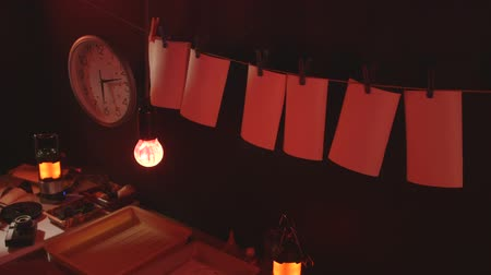 negatives : Temporary amateur photographer darkroom with photographic equipment and red safelight at home
