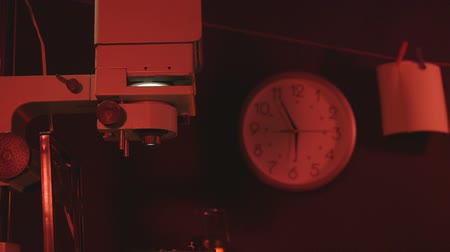 negatives : Ticking clock in temporary amateur photographer darkroom  with red safelight and photographic equipment Stock Footage
